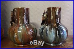 Superbe paire de vases vernissés bleu avec visages d'enfants dans des feuilles